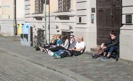 Sitzen auf der Pflasterung und Entspannung in der Sonne Stockbilder