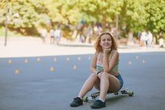 Sitzen auf einem Skateboard stockbild