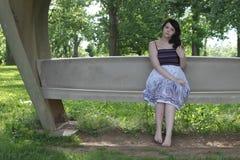 Sitzen auf einer Bank Stockfotos