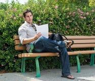 Sitzen auf Park-Bank lizenzfreies stockbild