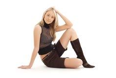 Sitzen blond in den braunen kurzen Hosen und in den Stiefeln Stockbild