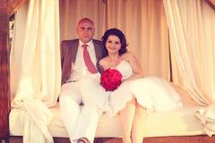 Sitzen der Braut und des Bräutigams im Freien auf einem Bett Lizenzfreies Stockbild