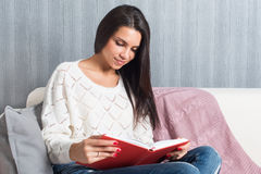 Sitzen der jungen Frau las Buchcouchsofa zu Hause Lizenzfreie Stockfotos