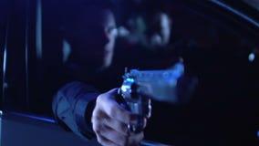 Sitzen der Polizisten im Dienst im Auto, drohender Verbrecher mit Pistole, Hinterhalt stock footage
