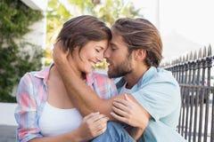 Sitzen des glücklichen Paars und Umarmung Stockfoto