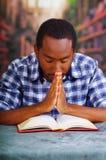 Sitzen des religiösen Mannes beim Beten und Ablesen vom offenen Buch auf Schreibtisch in der Front, Religionskonzept Lizenzfreies Stockfoto