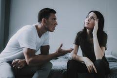 Sitzen des verheirateten Paars auf Gray Bed und der Argumentierung lizenzfreies stockfoto