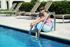 Sitzen durch das Pool stockbilder