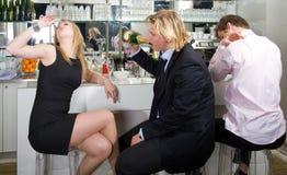 Sitzen an einem Stab und an einem trinkenden Champagner Lizenzfreie Stockbilder