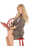 Sitzen graues Geschäftskleid der Frau Tablettenumkippen stockfoto
