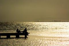 Sitzen im Dock einer Bucht Stockfotos