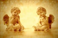 Sitzen mit zwei nettes Engeln Stockbilder