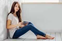 Sitzen nahe der Wand und Blicke im Tablet Lizenzfreie Stockfotos