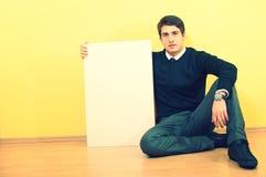 Sitzen und Holding des jungen Mannes eine unbelegte Anschlagtafel stockfoto
