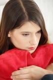 Sitzen und squeezeing Kissen der traurigen Frau. Lizenzfreies Stockfoto