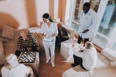 Sitzende alte Frau Doktor und Krankenschwester Stand Nearby stockfotos