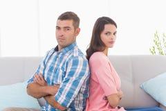 Sitzende Arme der verärgerten Paare gekreuzt auf Sofa Lizenzfreie Stockbilder