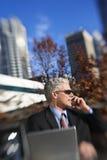 Sitzende Außenseite des Geschäftsmannes, die auf Mobiltelefon mit Gebäuden spricht Stockbild