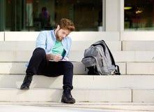Sitzende Außenseite des männlichen Studenten auf dem Campus, die Anmerkungen liest Stockbilder