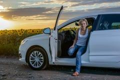 Sitzende Aufwartung der recht blonden Frau in ihr Auto Lizenzfreie Stockbilder