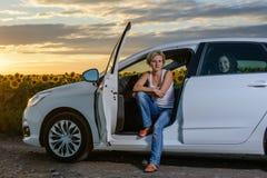 Sitzende Aufwartung der recht blonden Frau in ihr Auto Stockfotografie