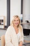 Sitzende Büro-Frau, die an ihrem Schreibtisch sich lehnt Stockbilder