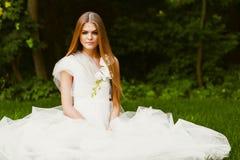 Sitzende blonde Frau mit den Fliegenblumenblättern Lizenzfreie Stockfotografie