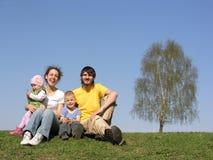Sitzende Familie mit zwei Kindern. Frühling. Lizenzfreie Stockfotografie