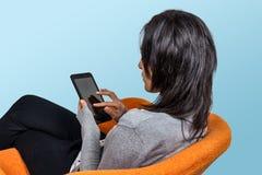 sitzende Frau, die Tablette verwendet rührende Oberfläche des tragbaren Geräts stockfoto