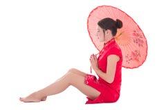 Sitzende Frau im roten Japanerkleid mit dem Regenschirm lokalisiert auf wh Lizenzfreie Stockfotografie