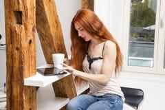 Sitzende Frau mit einem Glas des Getränks und des Tablets Lizenzfreie Stockfotos