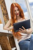 Sitzende Frau mit einem Glas des Getränks und des Tablets Lizenzfreies Stockbild