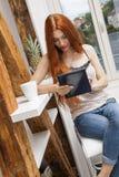 Sitzende Frau mit einem Glas des Getränks und des Tablets Stockbild
