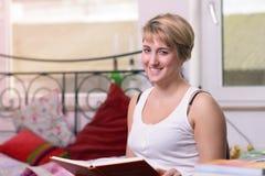 Sitzende glückliche blonde Frau, die ein Buch hält Lizenzfreies Stockbild