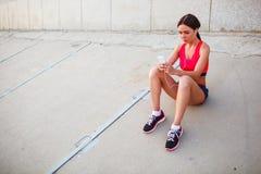 Sitzende hörende Musik der Läuferfrau Lizenzfreie Stockfotos