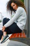 Sitzende junge sportliche Frau lizenzfreies stockfoto