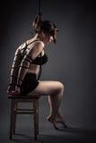 Sitzende Knechtschaft des schönen weiblichen Sklaven ropes auf Stuhl lizenzfreie stockfotografie