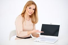 Sitzende lächelnde Frau, die Laptop auf Tabelle zeigt Stockfoto