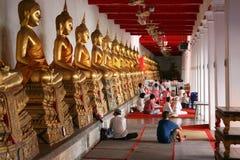 Sitzende Leute mit dem Sitzen von Buddha Stockfoto