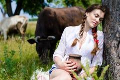 Sitzende müde nahe Kühe der jungen Frau in der Landschaft Stockfotografie