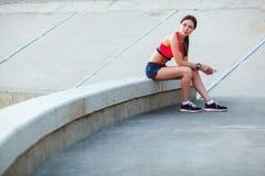 Sitzende müde sportliche Frau Stockfotografie