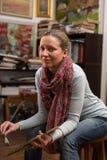 Sitzende Malerei des attraktiven weiblichen Malers in einer Galerie Lizenzfreie Stockfotos