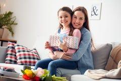 Sitzende Mutter des Mutter- und Tochterzu hause Geburtstages, die das Tochterholding-Geschenkboxlächeln glücklich umarmt stockbild