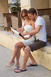 Sitzende Paare, die Wegkarte oder -führer in den Händen betrachten. Stockbild