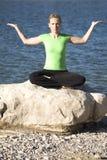 Sitzende Palme der Yogafrau oben durch Wasser Stockfotos