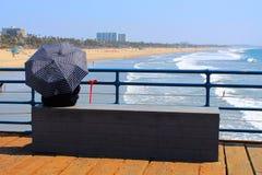 Sitzende Regenschirmsonne Santa Monica Dame Stockfotos