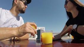 Sitzende Tabelle der reizenden Paare, die den Orangensaft spricht trinkt, Tageshimmel feiernd stock video