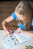 Sitzende Tabelle des hübschen Mädchens des Porträts mit erwachsenem Malbuch zeichnet an Stockfotografie