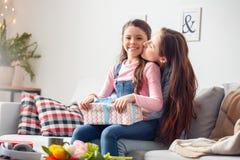 Sitzende Tochter des Mutter- und Tochterzu hause Geburtstages, die Präsentkarton geküsst von der Mutter hält lizenzfreies stockbild