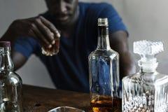 Sitzende trinkende schlechte Gewohnheit der alkoholischen Suchts des Whiskys des Mannes der afrikanischen Abstammung stockbild